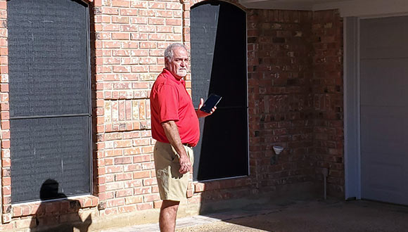 A home inspector in front of a house, going over the checklist.